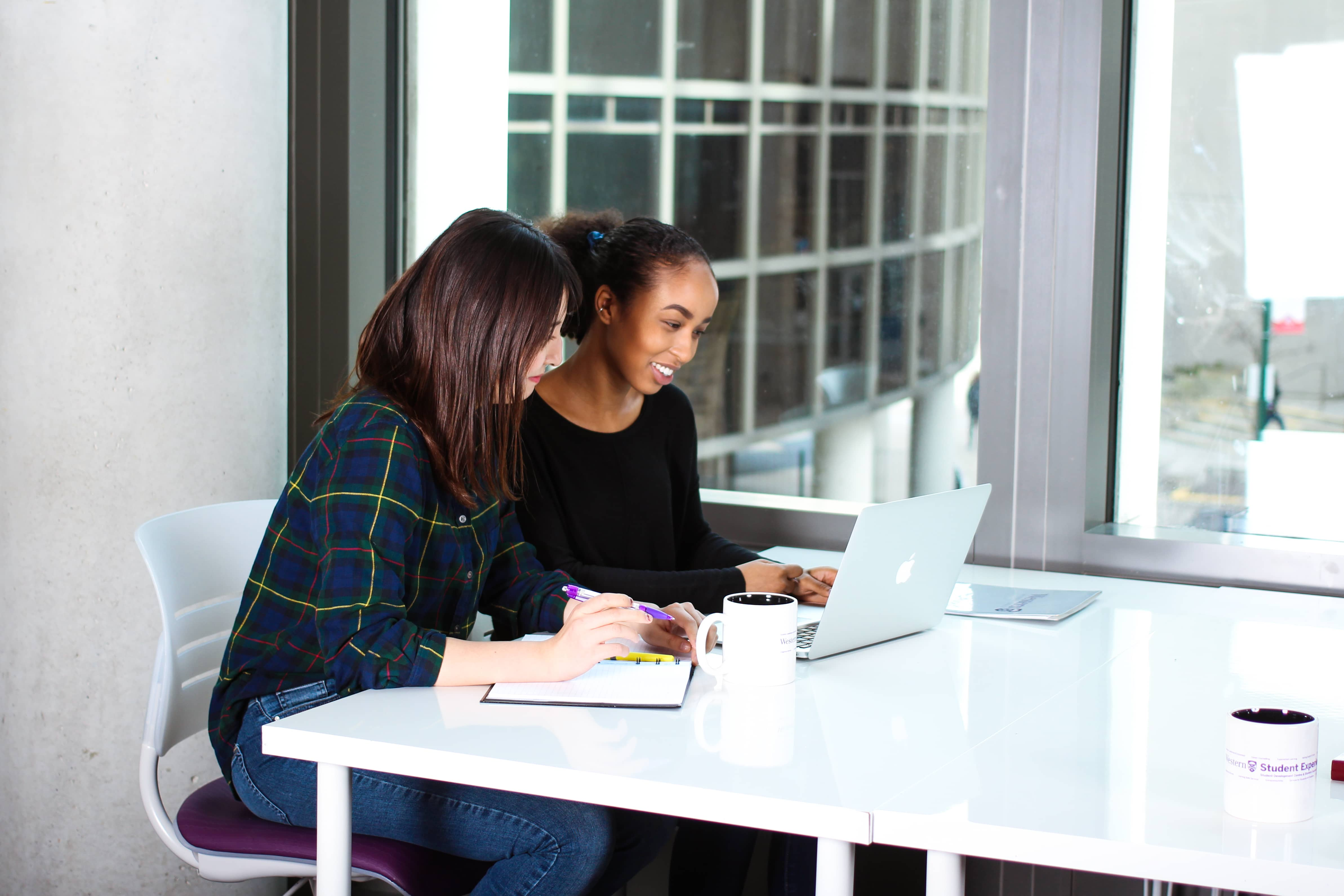 Two students work together at a laptop